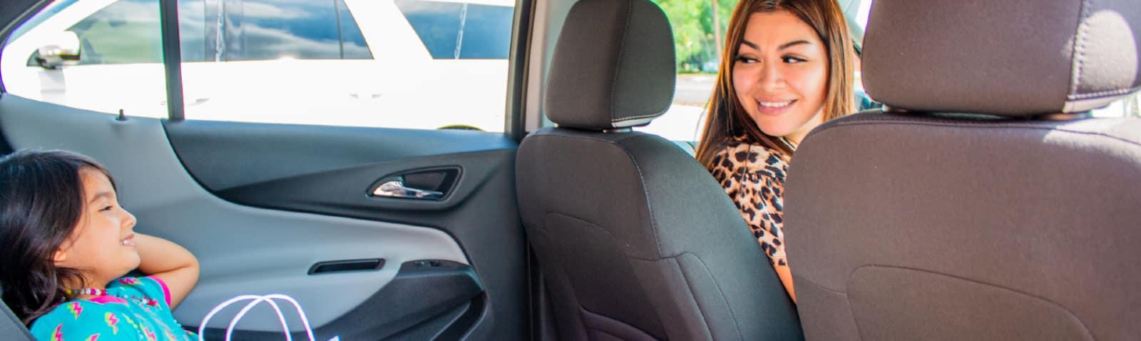 A happy girl getting inside a car.