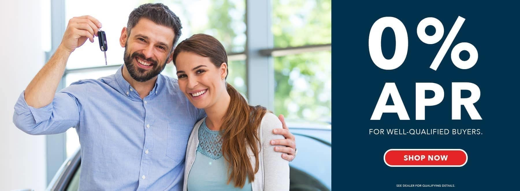 A couple holding a car key and smiling, 0% APR banner