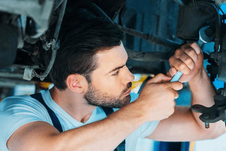 service technician loosens bolt on car undercarriage - mobile