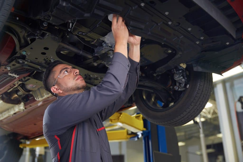 Male Mechanic changing oil