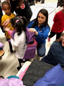 Volunteer putting coat on child