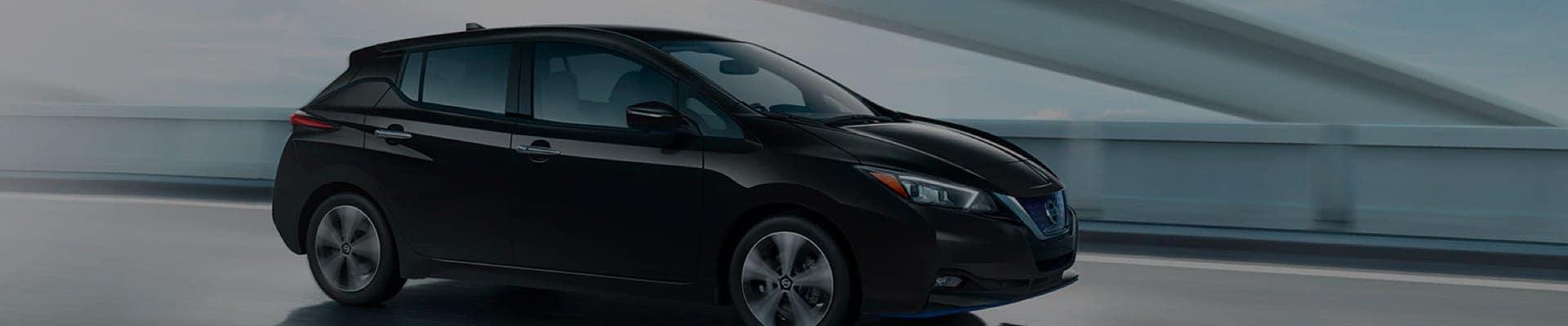 Black Nissan LEAF driving through city at night