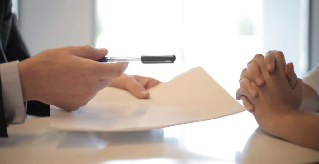 Car Dealer and Customer Reviewing Loan Contract Across Table