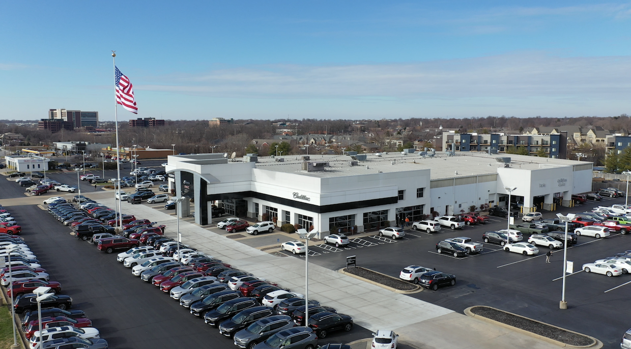 An aerial exterior shot of a Cadillac dealership during the day.