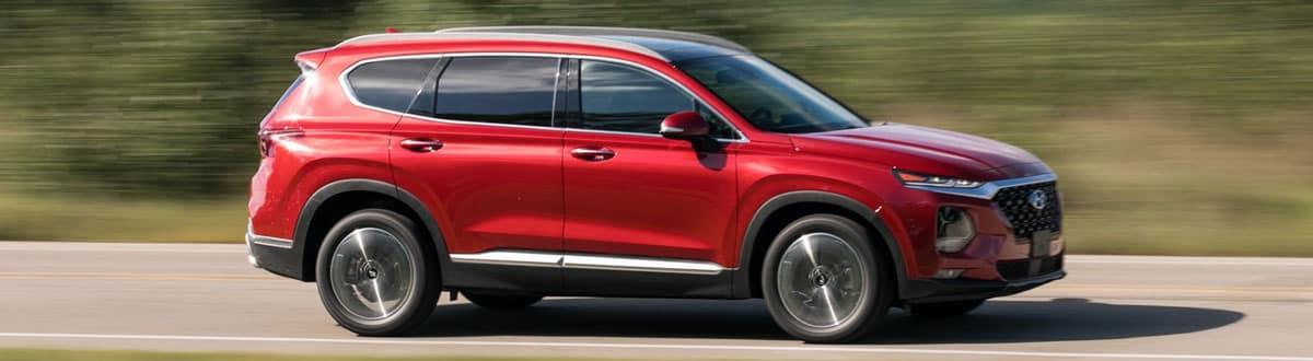 Red Hyundai Santa Fe Driving Down Road